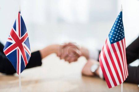 Photo pour Une focalisation sélective des drapeaux de l'usa et du royaume uni près des diplomates serrant la main - image libre de droit