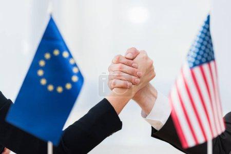 Photo pour Foyer sélectif des diplomates tenant la main près des drapeaux des Etats-Unis et de l'Union européenne - image libre de droit