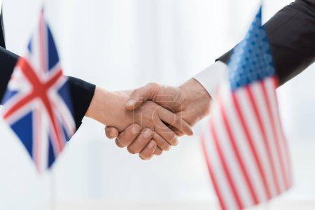 Foto de Enfoque selectivo de diplomáticos que se estrechan las manos cerca de banderas de uso y reino unido - Imagen libre de derechos