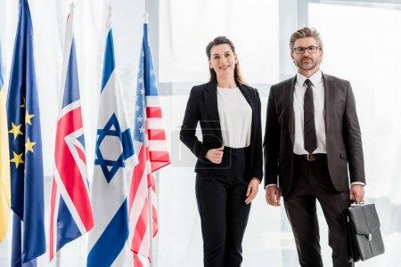 Photo pour Ambassadeurs joyeux se tenant près des drapeaux de différents pays - image libre de droit