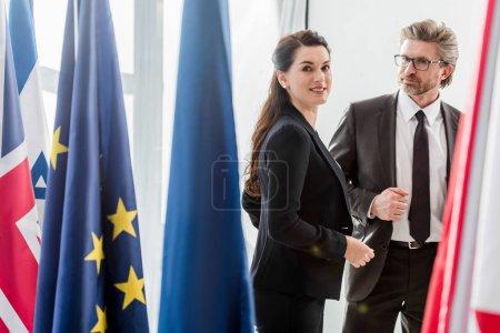 Photo pour Happy woman près d'un diplomate barbu et de drapeaux à l'ambassade - image libre de droit