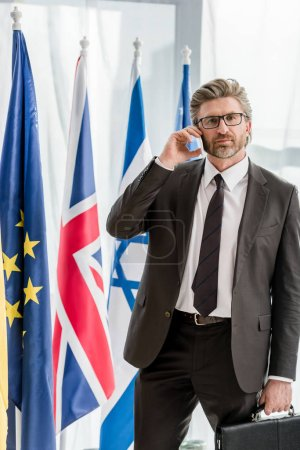 Photo for Handsome diplomat in glasses talking on smartphone near flags - Royalty Free Image