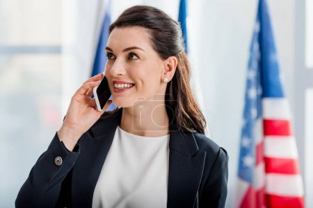 Photo for Happy diplomat talking on smartphone near american flag - Royalty Free Image