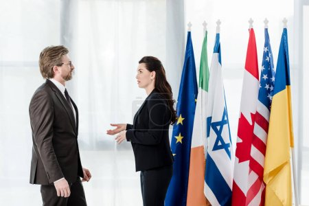 Photo for Side view of diplomats talking near flags in embassy - Royalty Free Image
