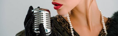 panoramic shot of woman touching retro microphone isolated on grey