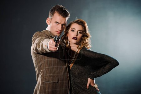 selective focus of dangerous gangster holding gun and standing near attractive woman  on black