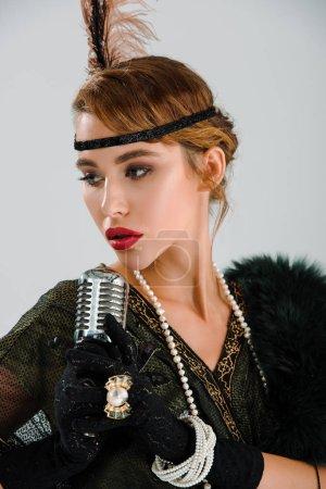 Photo pour Chanteuse attirante touchant un microphone rétro isolé sur gris - image libre de droit