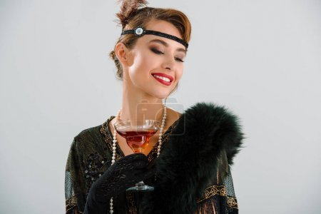 Photo for Cheerful aristocratic woman holding glass with drink isolated on grey - Royalty Free Image