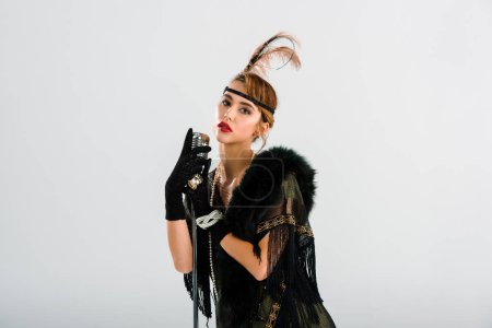 Photo pour Femme élégante debout et touchante microphone vintage isolé sur blanc - image libre de droit