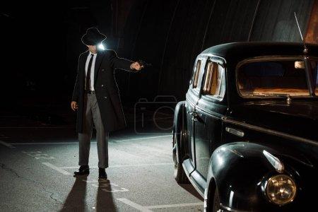 Photo pour Beau gangster en chapeau et manteau tenant une arme à feu près d'une voiture rétro - image libre de droit