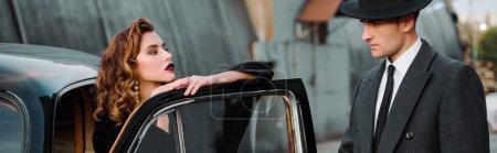 Foto de Foto panorámica del hombre guapo en el sombrero de pie cerca de la mujer atractiva en coche retro. - Imagen libre de derechos