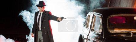 Photo pour Photo panoramique de gangster stylé en chapeau tenant un pistolet près de la voiture rétro sur noir avec la fumée - image libre de droit
