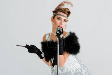 attractive woman singing while touching retro microphone and holding cigarette holder isolated on grey