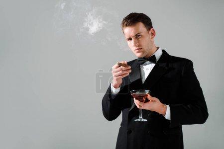 Photo pour Homme riche en costume avec boucle cravate verre avec alcool et cigare isolés sur gris - image libre de droit