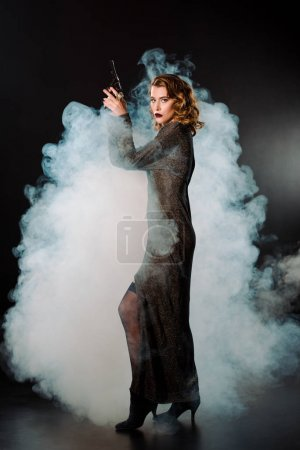 Photo pour Jolie femme tenant un fusil et se tenant debout avec de la fumée - image libre de droit