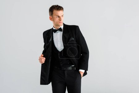 stylish man in suit and bow tie standing with hand in pocket isolated on grey