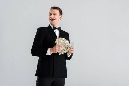 Photo pour Homme riche en costume tenant des billets de dollars isolés sur le gris - image libre de droit