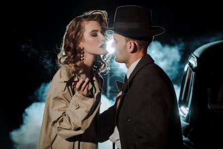 handsome gangster in hat looking at attractive woman near car on black with smoke
