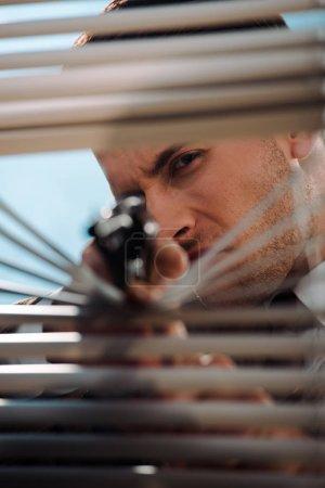 selective focus of dangerous man holding gun near window blinds