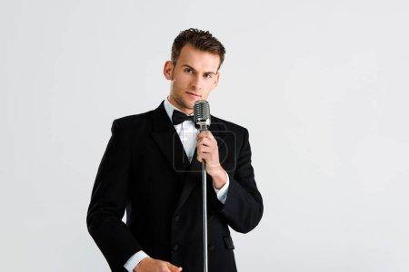 Photo pour Bel homme en costume touchant microphone rétro isolé sur blanc - image libre de droit