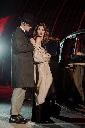 Photo pour Bel homme au chapeau vêtu d'un manteau sur une femme séduisante près d'une voiture - image libre de droit