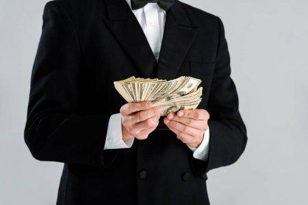 Foto de La visión descabellada del hombre rico en traje que tiene billetes de banco en dólares aislados en gris - Imagen libre de derechos