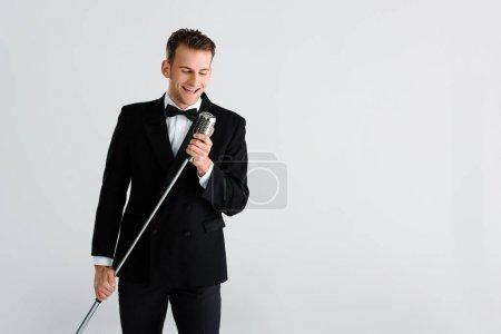 Photo pour Joyeux chanteur touchant un microphone rétro isolé sur gris - image libre de droit