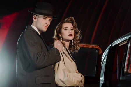 Photo pour Bel homme et chapeau habillé sur la femme près de la voiture retro - image libre de droit