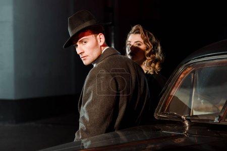 Photo pour Bel homme en chapeau et manteau debout près de la femme et voiture rétro - image libre de droit