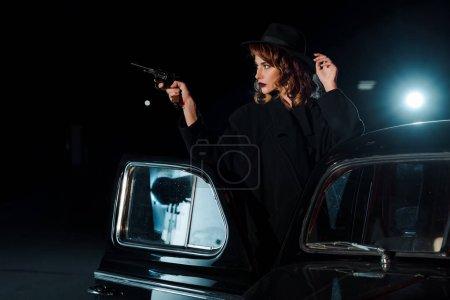 Photo pour Femme dangereuse en chapeau tenant une arme à feu près de la voiture rétro sur le noir - image libre de droit