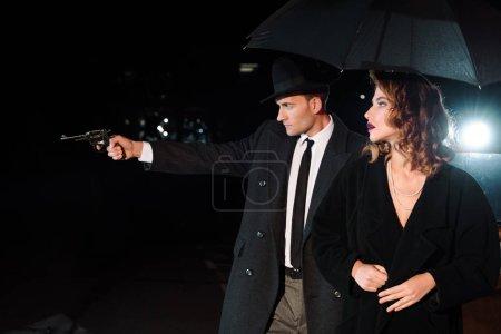 Photo pour Side view of dangerous man in hat holding gun near attractive girl and retro car on black - image libre de droit