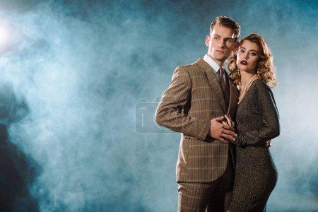 Photo pour Bel homme et belle femme en robe debout sur noir avec de la fumée - image libre de droit
