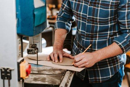 Photo pour Vue en coupe d'un menuisier tenant un crayon près d'un atelier de menuiserie électrique - image libre de droit