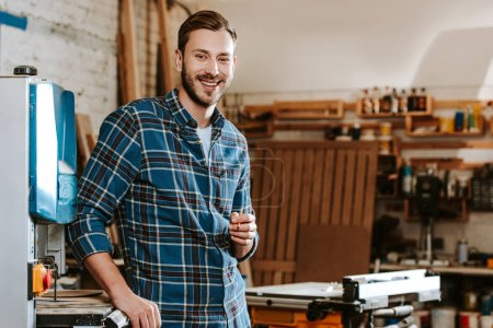 Photo for Cheerful carpenter holding pencil in workshop - Royalty Free Image