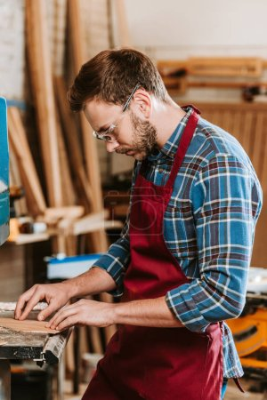 Photo for Handsome carpenter in protective glasses and apron in workshop - Royalty Free Image