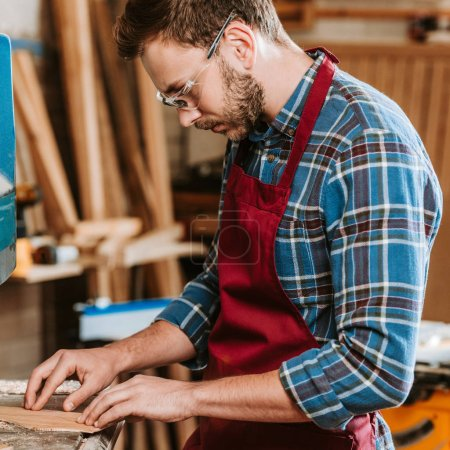 Photo for Bearded carpenter in protective glasses and apron in workshop - Royalty Free Image