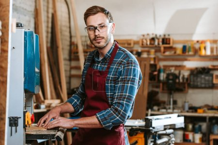 Photo for Selective focus of handsome man in goggles and apron in workshop - Royalty Free Image