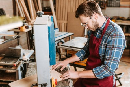 selective focus of bearded carpenter in safety glasses and apron using cnc machine