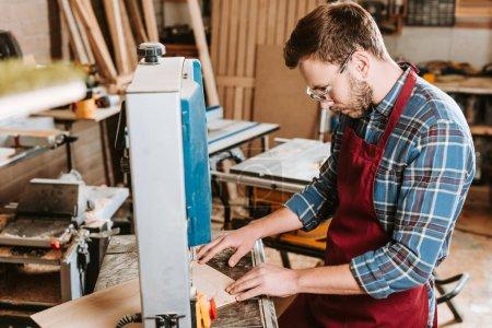 Photo pour Mise au point sélective du charpentier barbu dans les lunettes et le tablier de sécurité au moyen d'une machine à cnc - image libre de droit