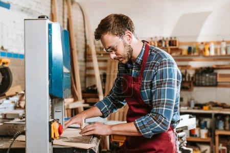 Photo pour Mise au point sélective du charpentier dans les lunettes et le tablier de sécurité au moyen d'une machine à cnc - image libre de droit