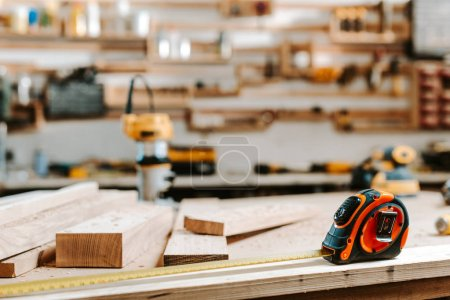 Photo pour Mise au point sélective du ruban à mesurer près des planches de bois sur la table - image libre de droit