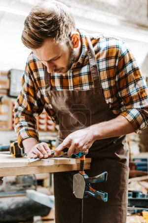 Photo for Bearded carpenter in brown apron carving wood in workshop - Royalty Free Image