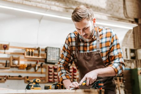Photo for Bearded carpenter holding chisel while carving wood in workshop - Royalty Free Image