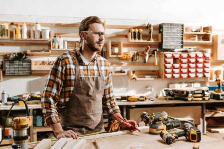 Photo for Handsome carpenter in goggles standing near table and equipment - Royalty Free Image