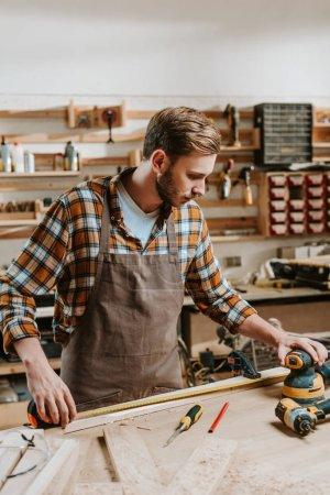 Photo pour Beau charpentier en tablier brun mesurant la planche de bois - image libre de droit
