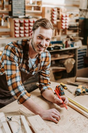 Photo for Cheerful woodworker holding pencil near wooden plank and measuring tape - Royalty Free Image