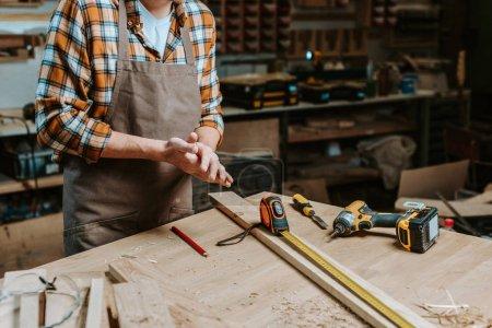 Photo pour Vue en coupe d'un menuisier sur un tablier debout avec les mains serrées près de la table avec des outils - image libre de droit