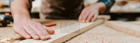 Photo for Panoramic shot of carpenter touching wooden plank - Royalty Free Image