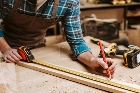 Photo for Cropped view of carpenter measuring plank with tape-measure in workshop - Royalty Free Image