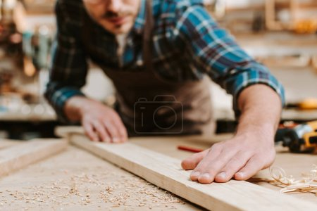Photo for Cropped view of carpenter touching wooden plank - Royalty Free Image
